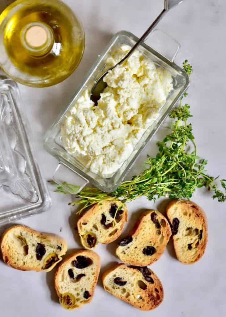 homemade ricotta cheese with olive oil, herbs, and olive loaf