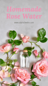 A vial with homemade rose water placed flat on a gray surface and surrounded with pink roses