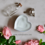 A heart shaped bowl filled with rose water a glass vial next to it and a bunch of pink roses