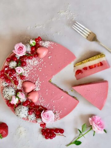 Layered strawberry tart decorated with red berries and dragon fruit balls with two slices cut off