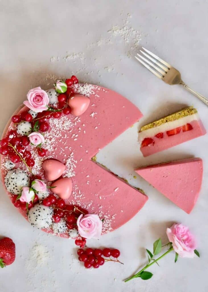 Two-layer Vegan strawberry tart with a pistachio & Almond crust and coconut & strawberry layered filling with fresh strawberries. A delicious, decadent Vegan dessert! with a couple of slices cut out of it.