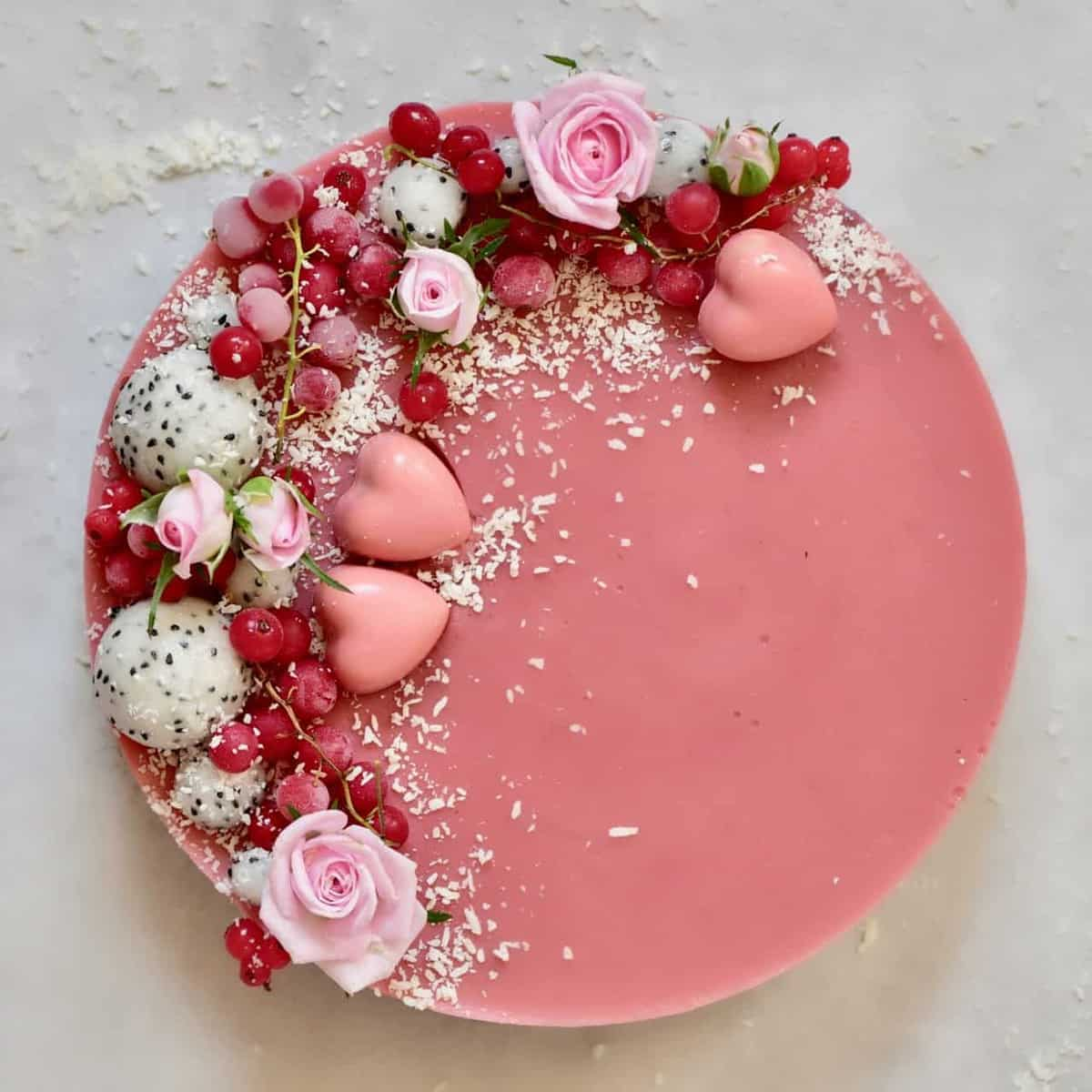 two-layered coconut and strawberry tart topped with coconut, dragon fruit, red berries and edible roses