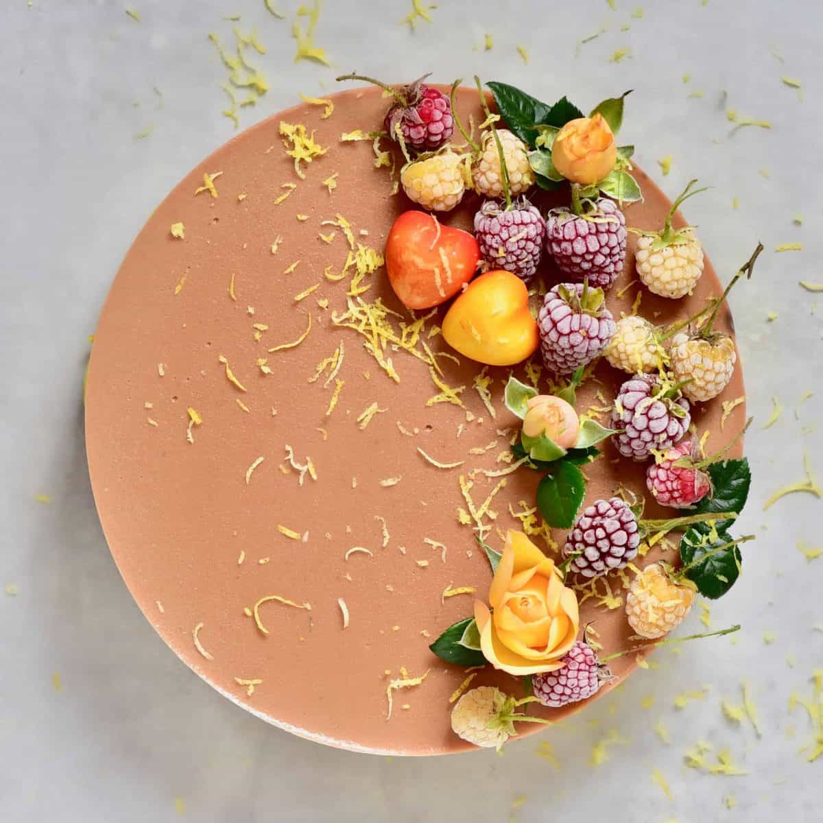 Two-layer Raspberry Peach & Lemonade Tart topped with frozen berries, edible flowers and lemon zest