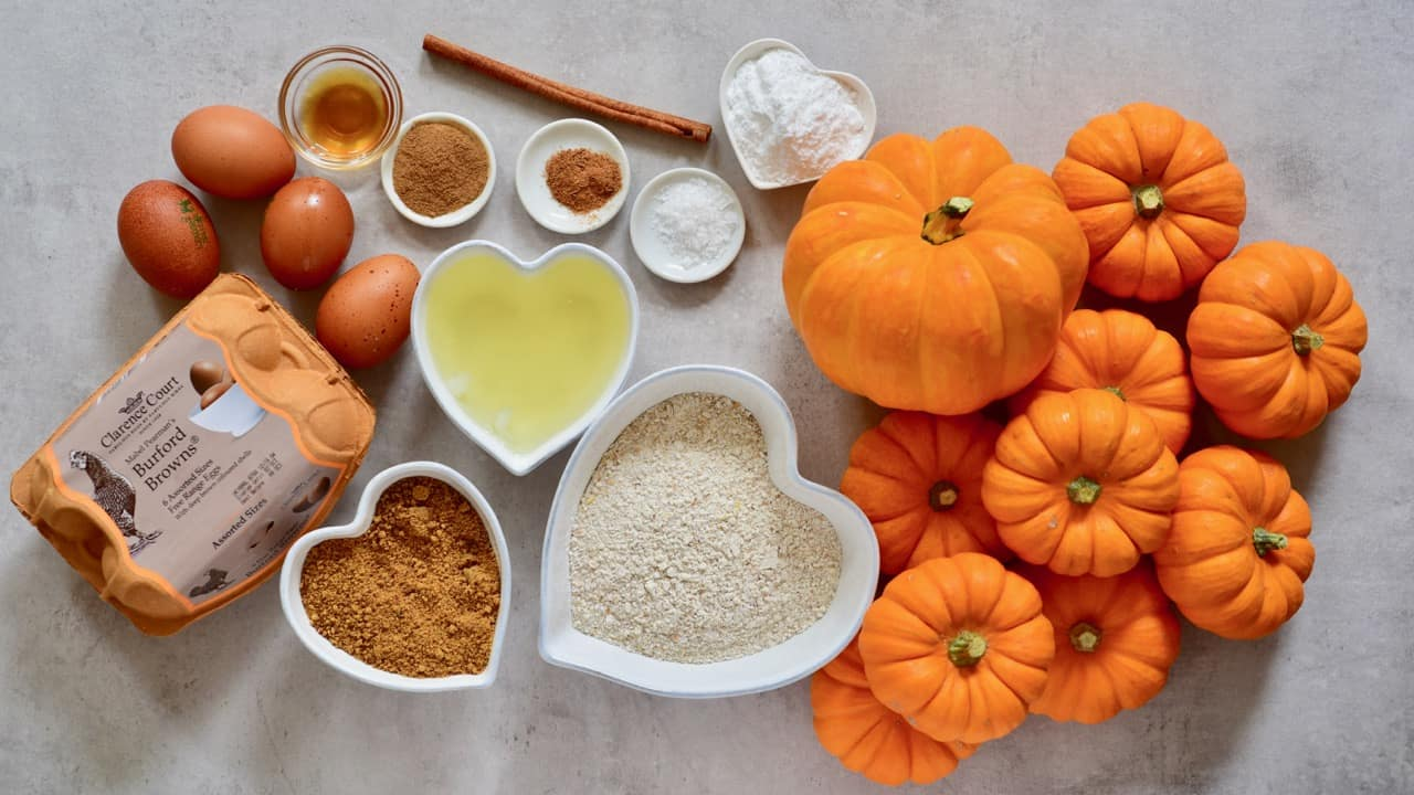 Ingredients for mini pumpkin cakes served inside pumpkins with coconut cream frosting and topped with pecans and date syrup. A delicious semi-sweet autumn/ fall dessert or thanksgiving dessert
