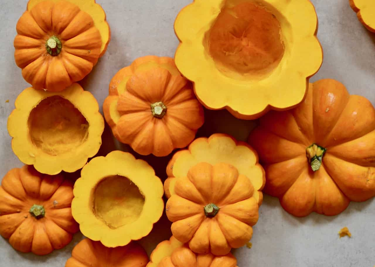 mini pumpkins for mini pumpkin cakes served inside pumpkins with coconut cream frosting and topped with pecans and date syrup. A delicious semi-sweet autumn/ fall dessert or thanksgiving dessert