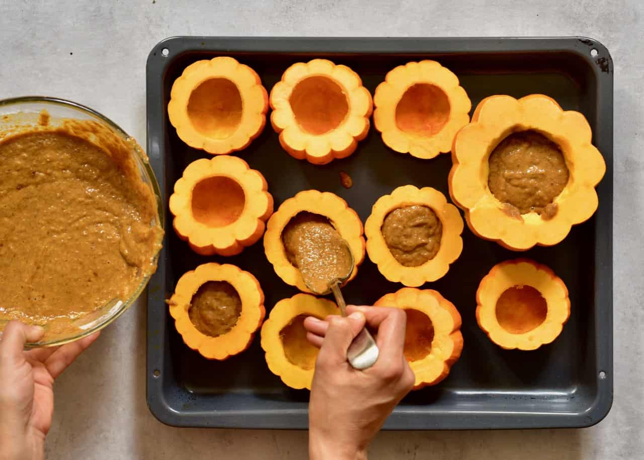 mini pumpkins being filled with pumpkin cake batter to make mini pumpkin cakes served inside pumpkins with coconut cream frosting and topped with pecans and date syrup. A delicious semi-sweet autumn/ fall dessert or thanksgiving dessert