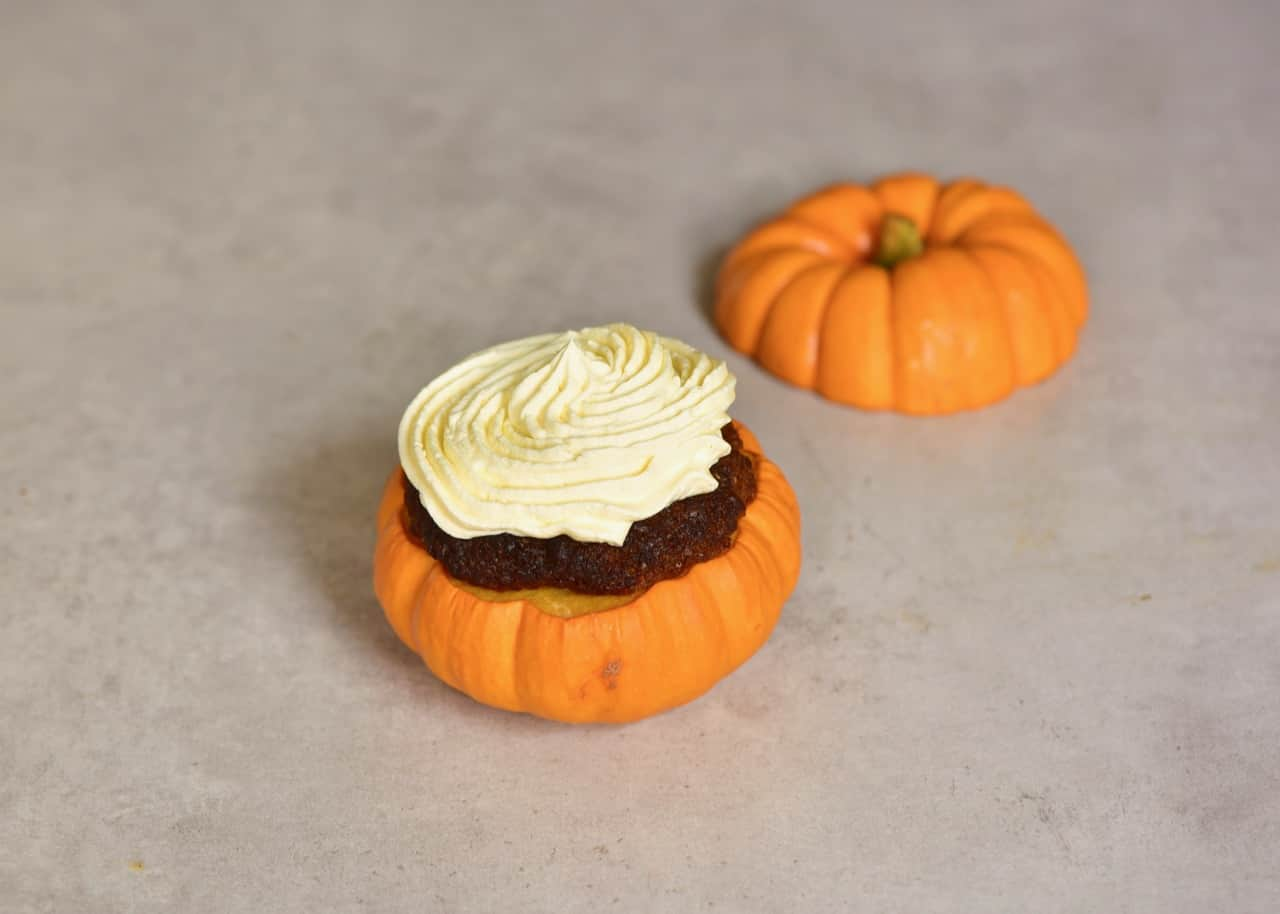 mini pumpkin cakes served inside pumpkins with coconut cream frosting and topped with pecans and date syrup. A delicious semi-sweet autumn/ fall dessert or thanksgiving dessert