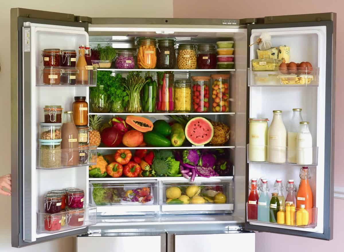 A refrigerator filled with fresh fruit and vegetables and other food