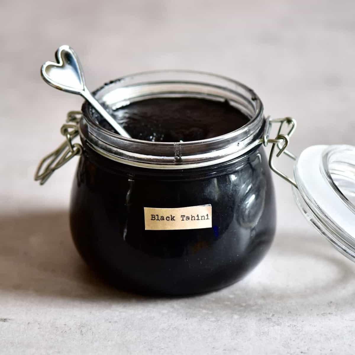 simple homemade black tahini recipe ( black sesame seed paste) in a jar
