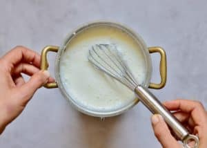 oat milk and cornstarch in a pan, being heated, with whisk