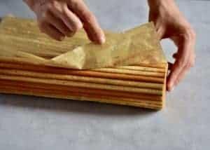 peeling parchment paper off freshly baked vegan loaf