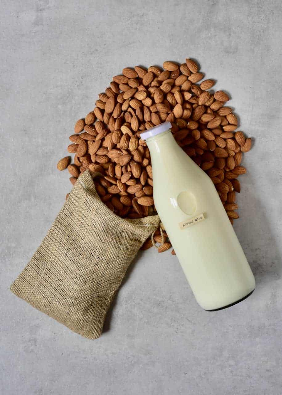 Almond Milk in a glass bottle placed over almond on a flat grey surface