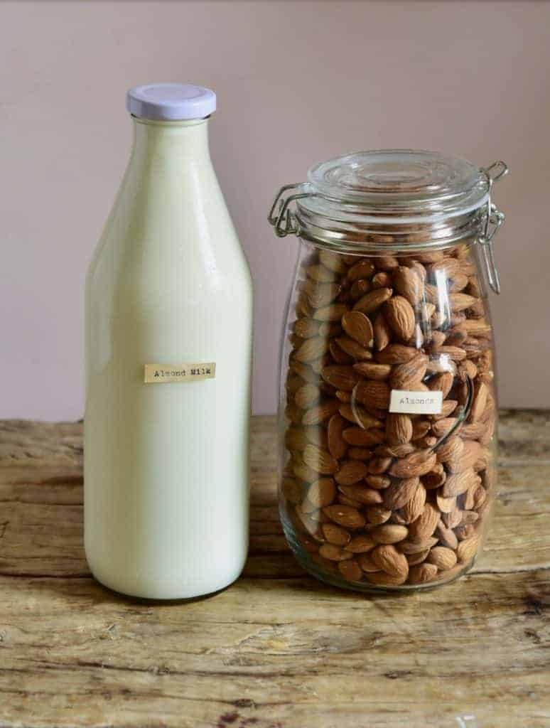 homemade almond milk in a bottle and almonds in a jar