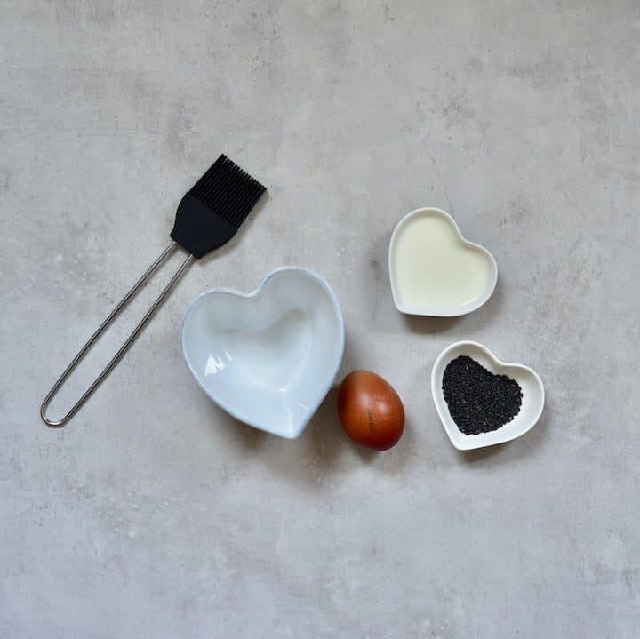 Ingredients for making black burger buns and a brush