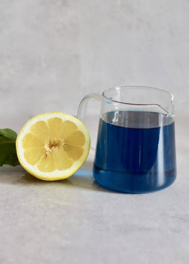 jug of concentrated butterfly pea tea next to half a lemon