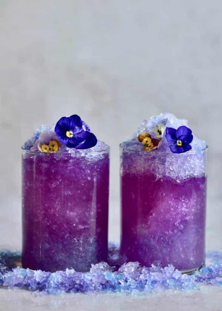 two glasses of butterfly pea flower lemonade with crushed ice and edible flowers