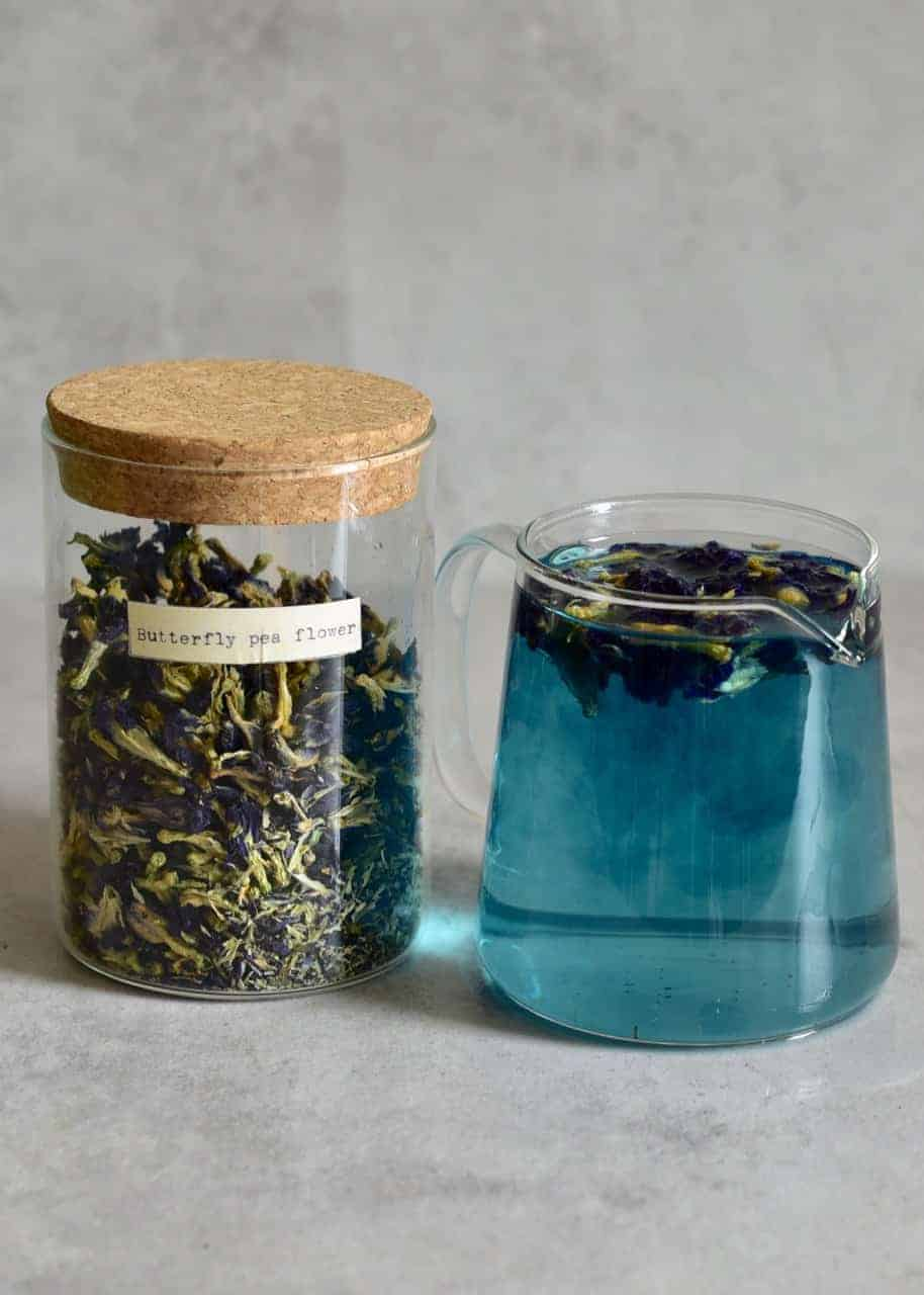 a jug of butterfly pea flower tea next to container of dried butterfly pea flower