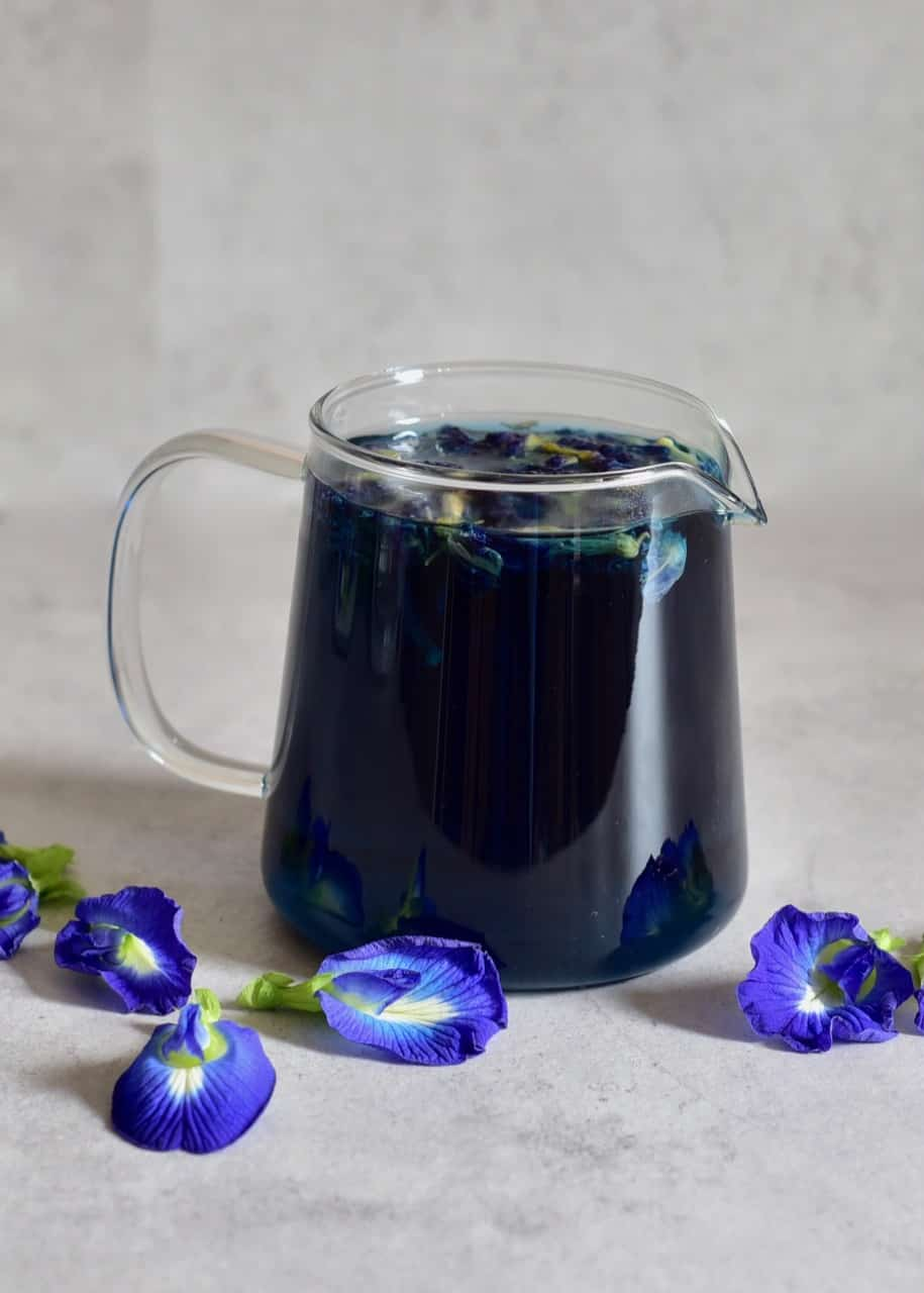 Deep blue Butterfly pea flower tea next to fresh butterfly pea flowers