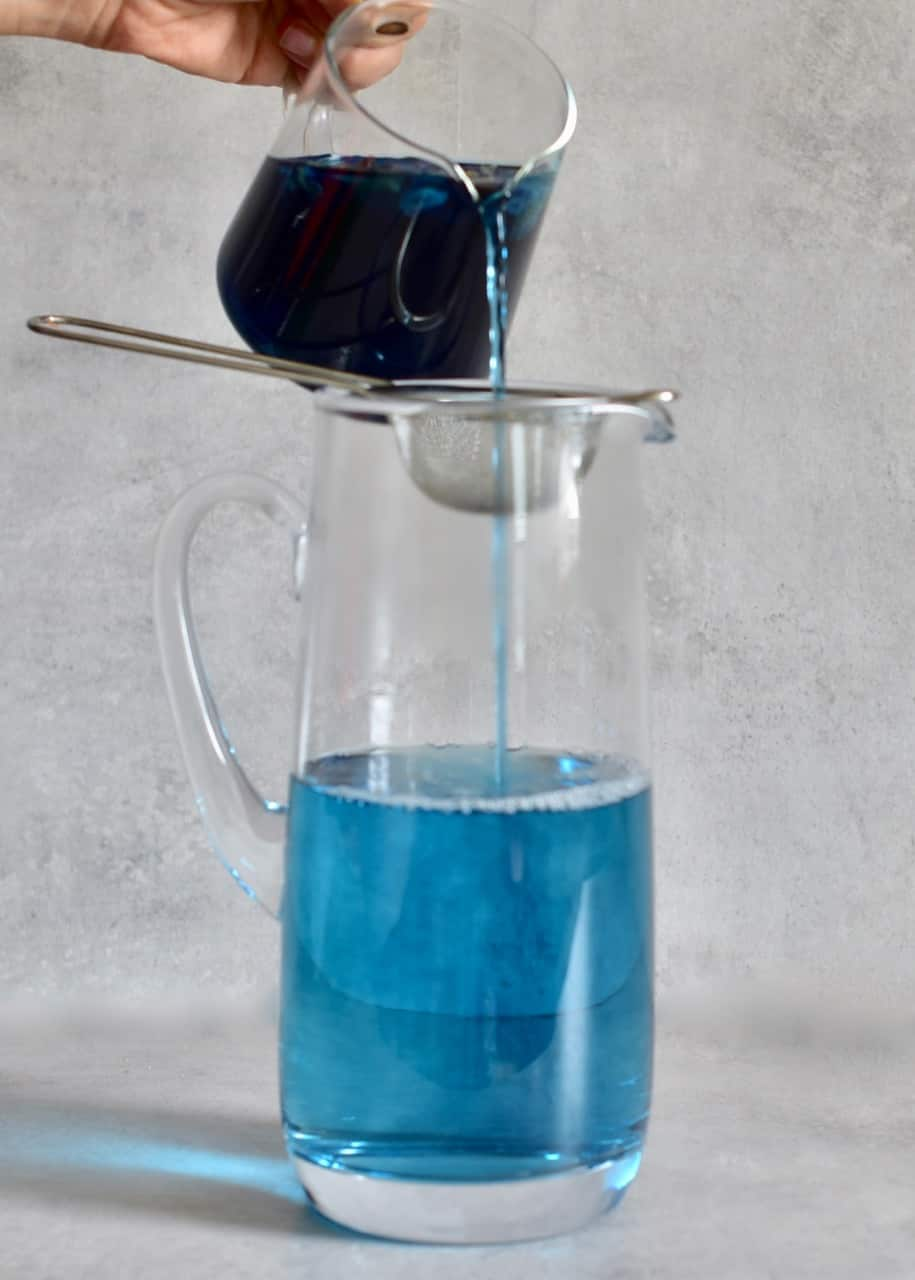 pouring concentrated butterfly pea tea into a large jug of water