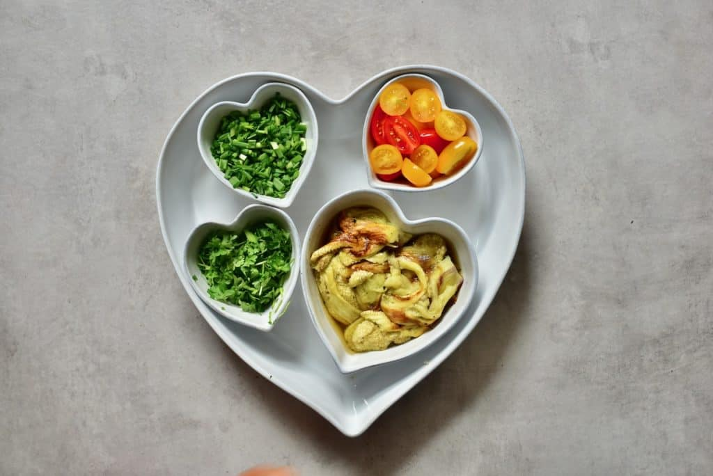 various salad ingredients in small heart-shaped tubs. tomato, herbs. green onion and aubergine