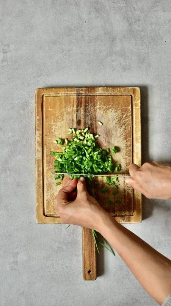chopping homegrown green onions for a salad