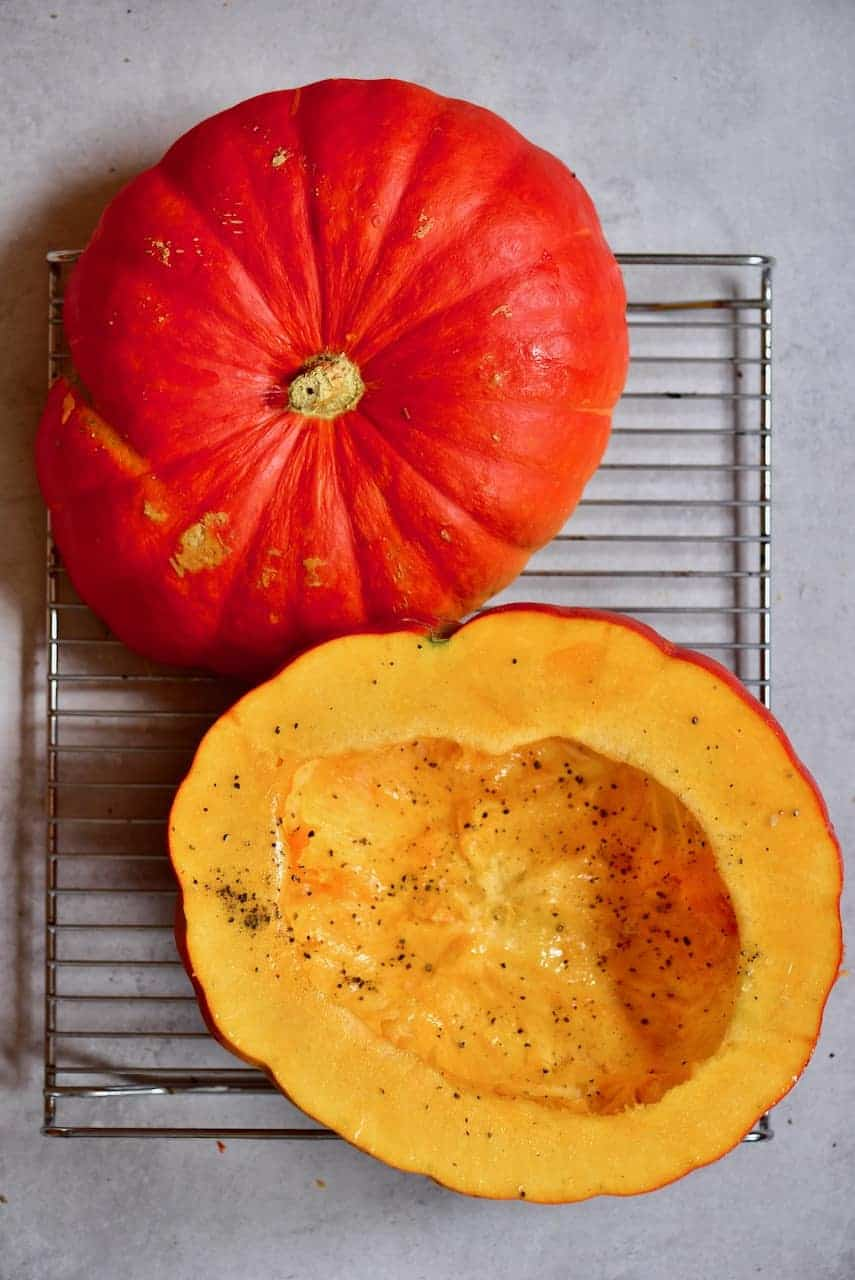 Sliced open pumpkin brushed with oil and sprinkled with pepper