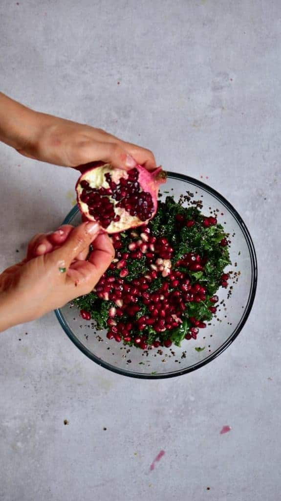 Opening a pomegranate over a quinoa kale salad
