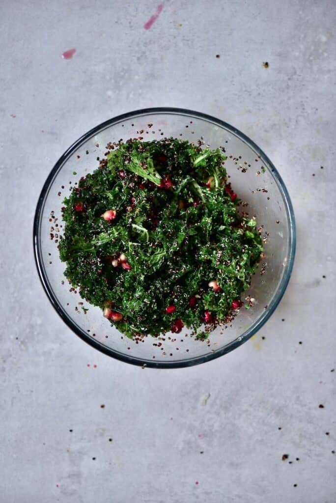 Quinoa kale salad with pomegranate seeds in a bowl