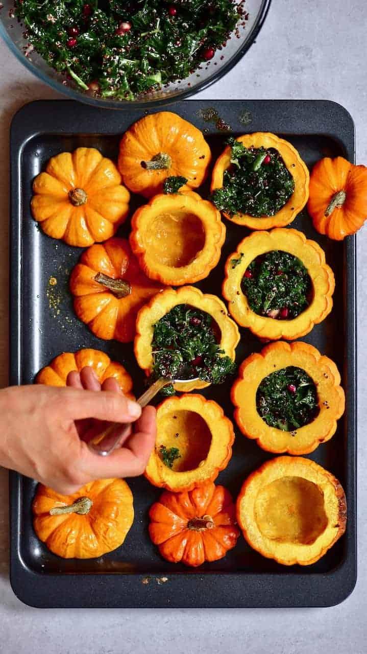 Filling baked mini pumpkins with kale salad