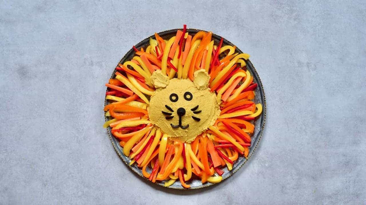 Delicious Vegan pumpkin spice hummus and veggies shapes as a lion