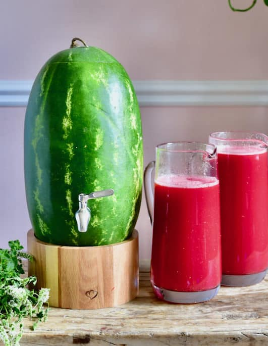 A watermelon drink dispenser and watermelon juice in glass pitchers
