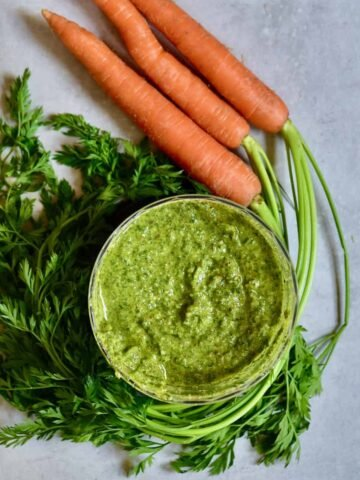Simple vegetarian carrot leaf pesto recipe to help reduce waste, Plus can be made into a vegan pesto too! A delicious blend of pistachios, pine nuts, olive oil, cheese, lemon and seasonings