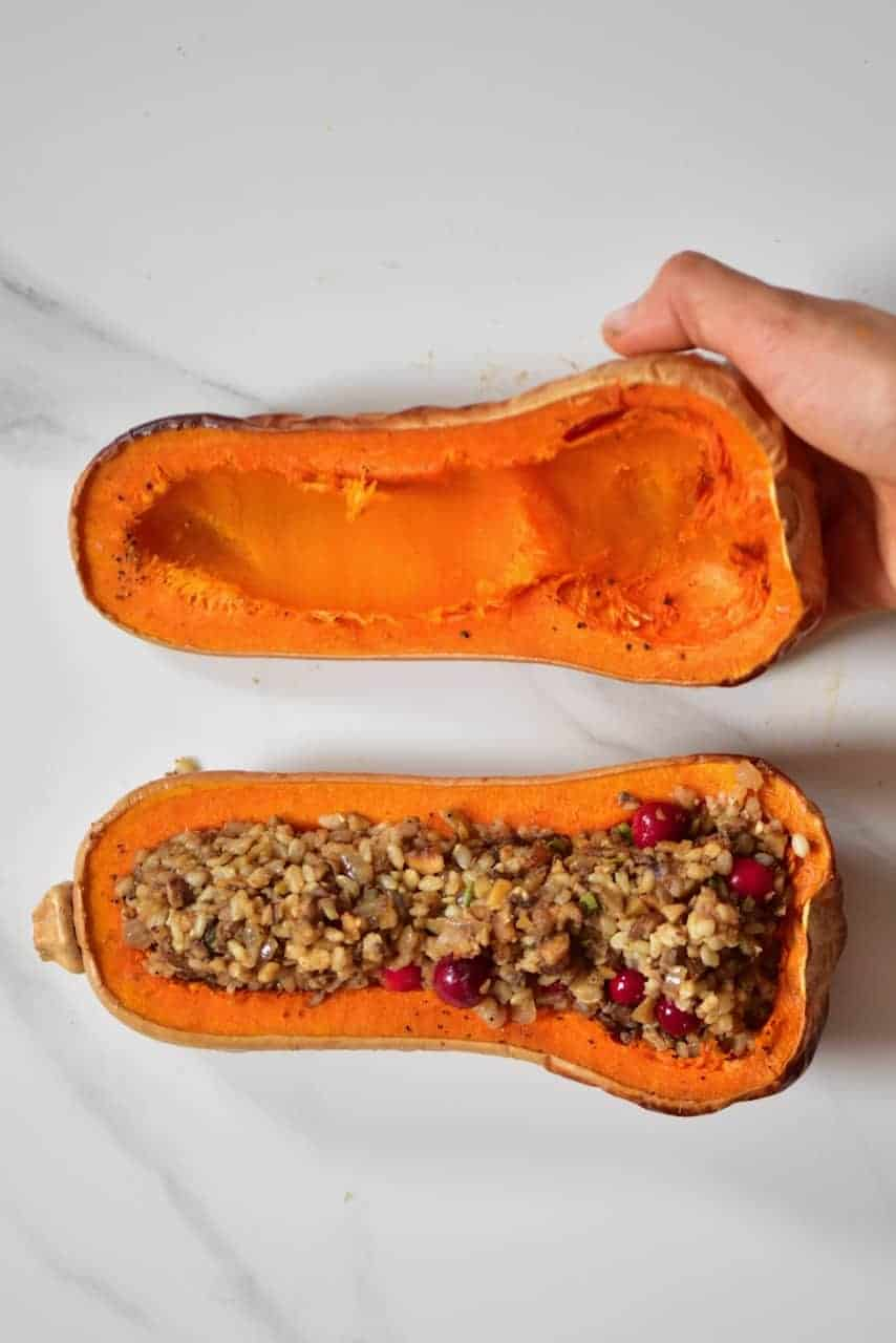 Butternut squash split in half and stuffed with rice and cranberries