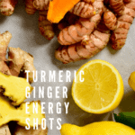 A small pile of turmeric root, a small pile of ginger root and one whole and one half lemon on a gray flat surface