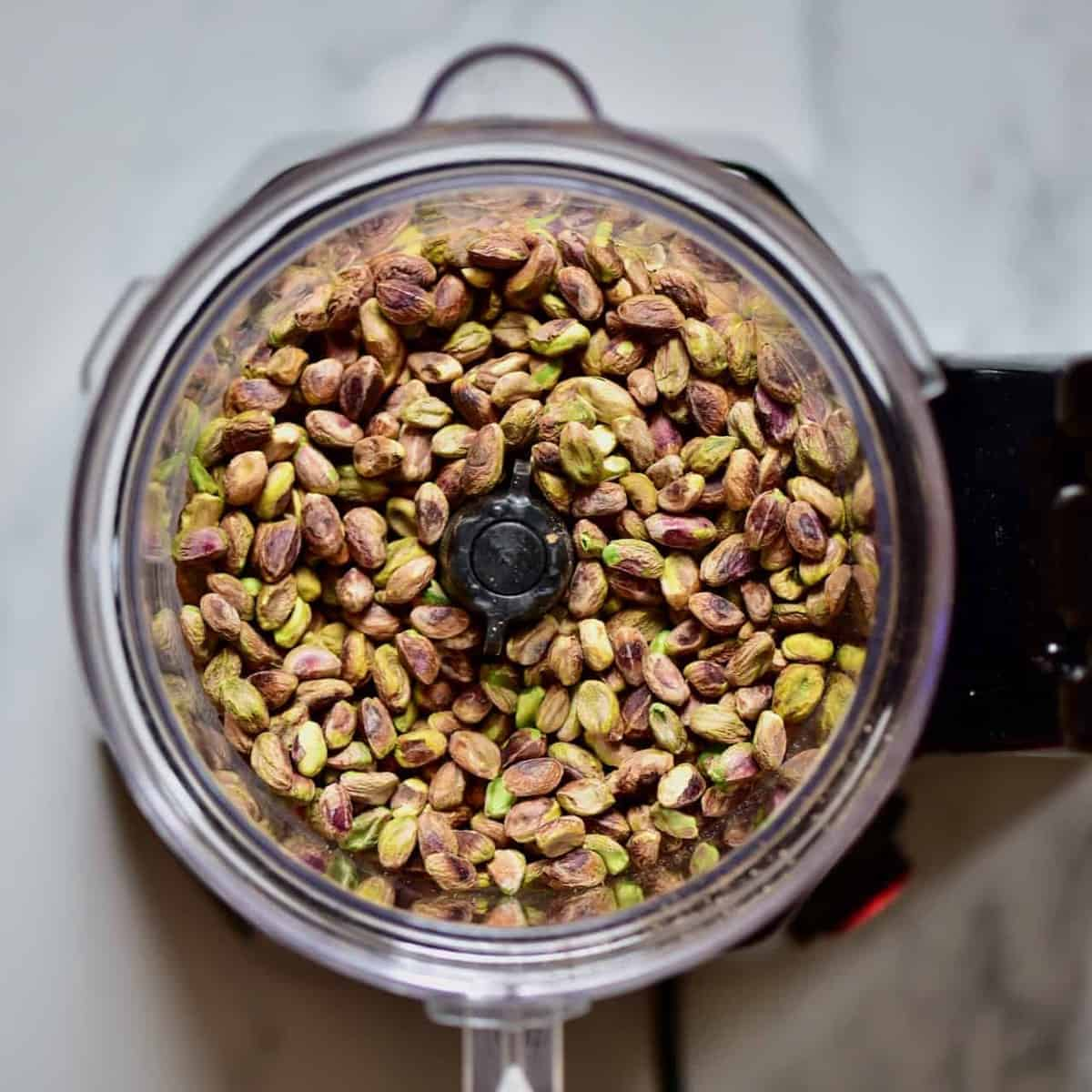 A blender filled with pistachios