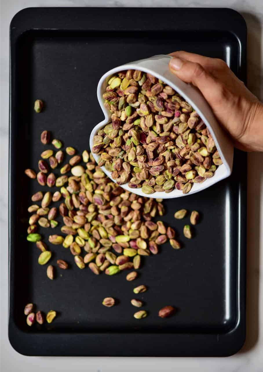 pouring pistachios in a baking tray