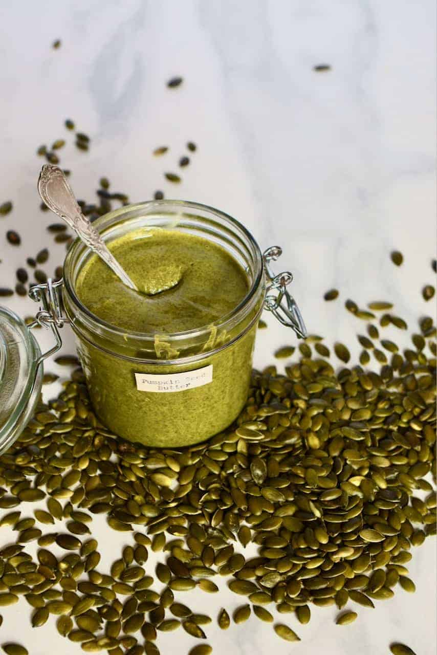 Pumpkin seed butter in a jar with a spoon and pumpkin seeds next to it on a flat surface