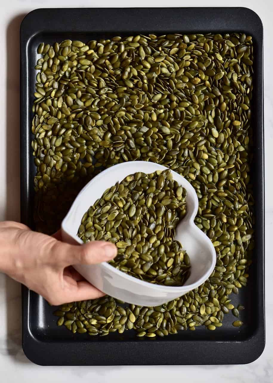 Filling up a baking tray with pumpkin seeds