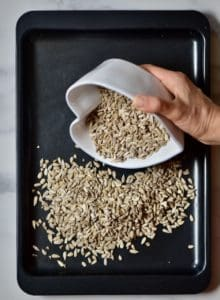 pouring sunflower seeds on a baking tray