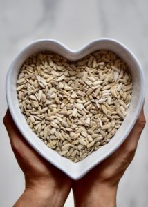 a heart shaped bowl with sunflower seeds