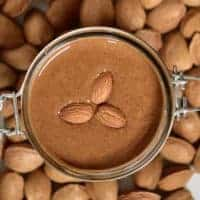 Top view of almond butter and three almonds in a jar and almonds around it on a flat surface