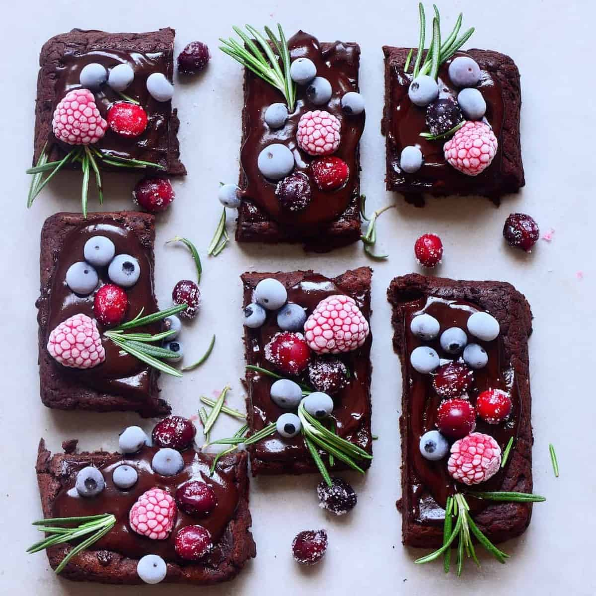 brownies topped with frozen berries and rosemary