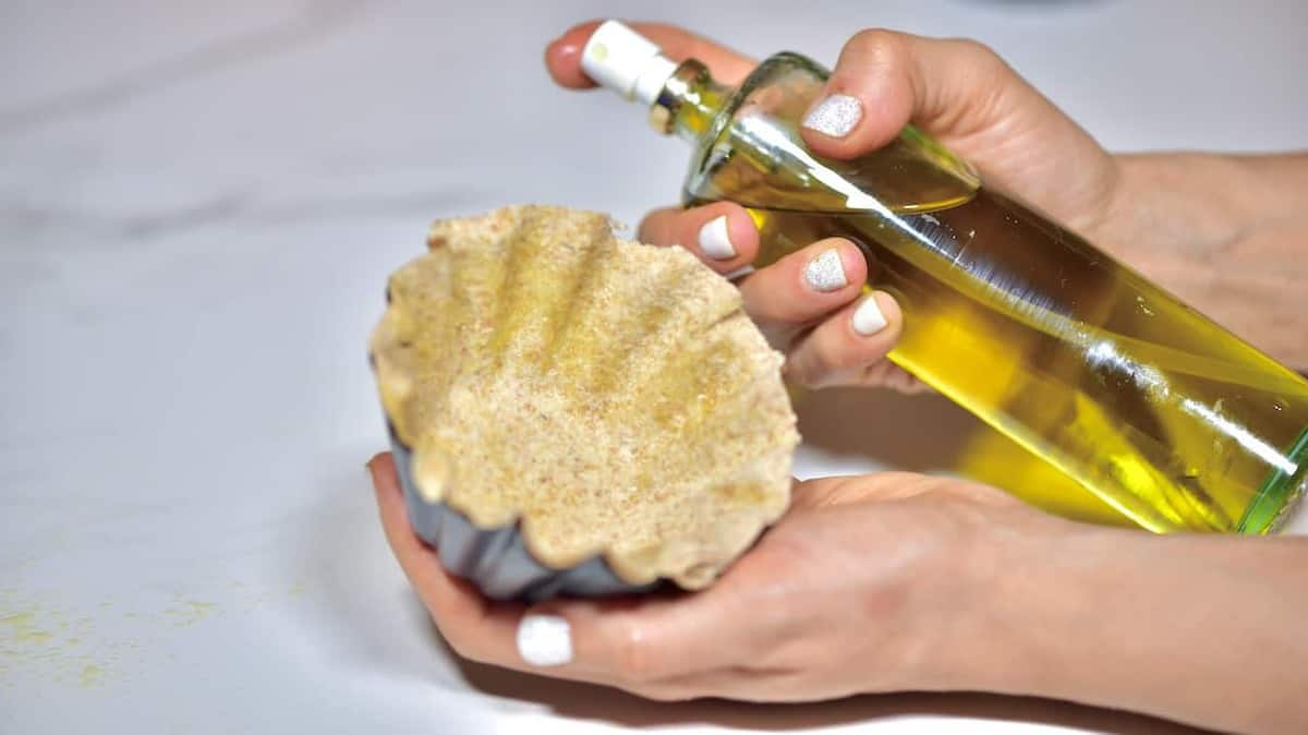 spraying olive oil on a tortilla cup, to bake