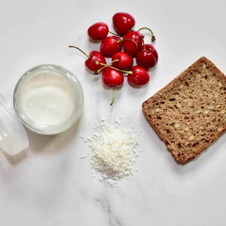 ingredients for healthy christmas toast recipe with homemade coconut yogurt and cherries.