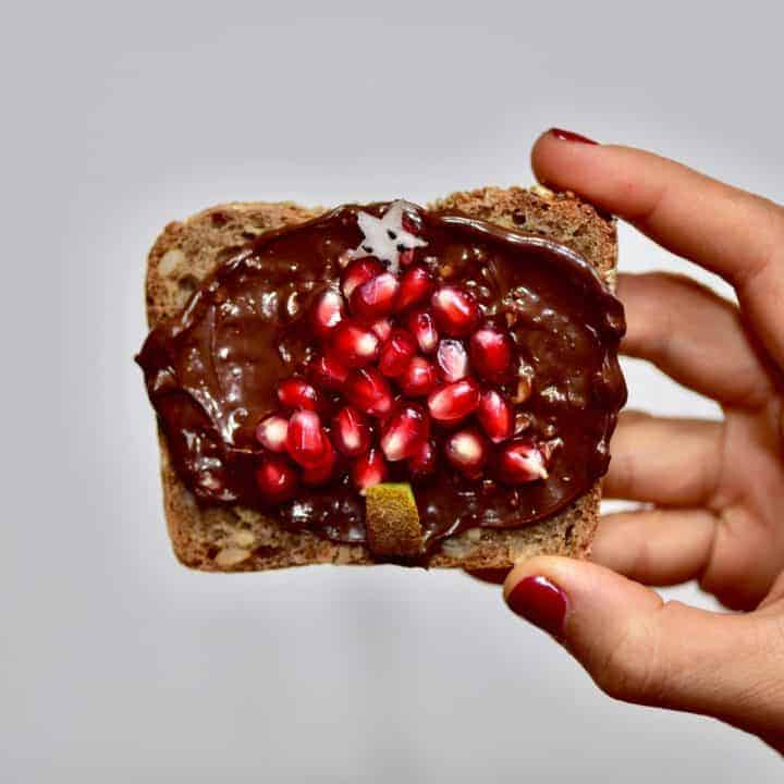Toast with homemade vegan nutella spread and pomegranate seeds