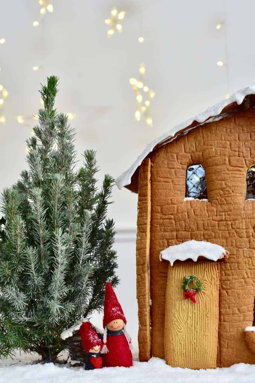 Gingerbread house with winter characters dressed in red