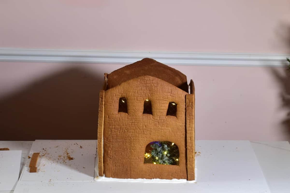 gingerbread house with four walls but no roof yet, decorated with small pine tree on inside