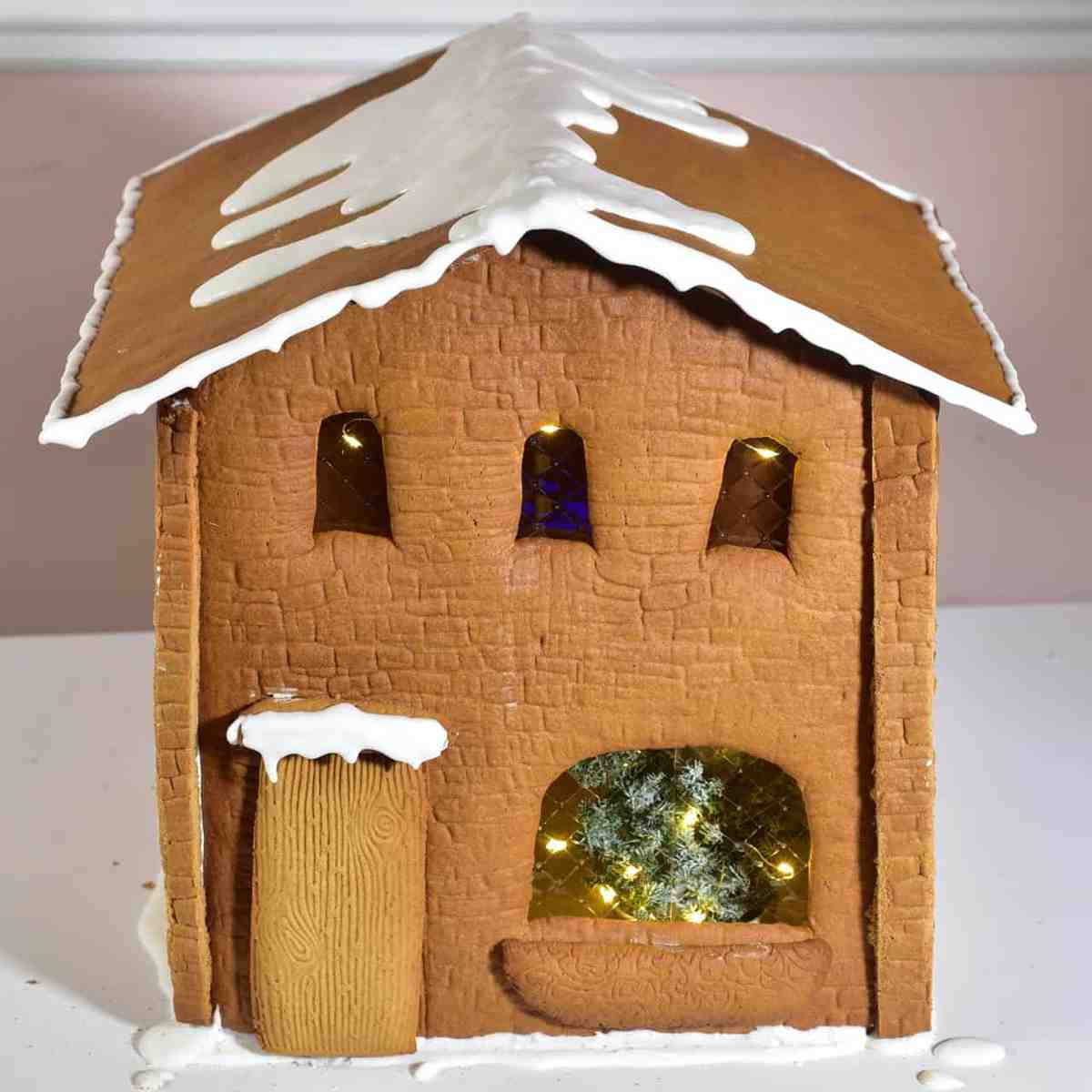 Gingerbread house decorated with some royal icing to imitate snow on the roof