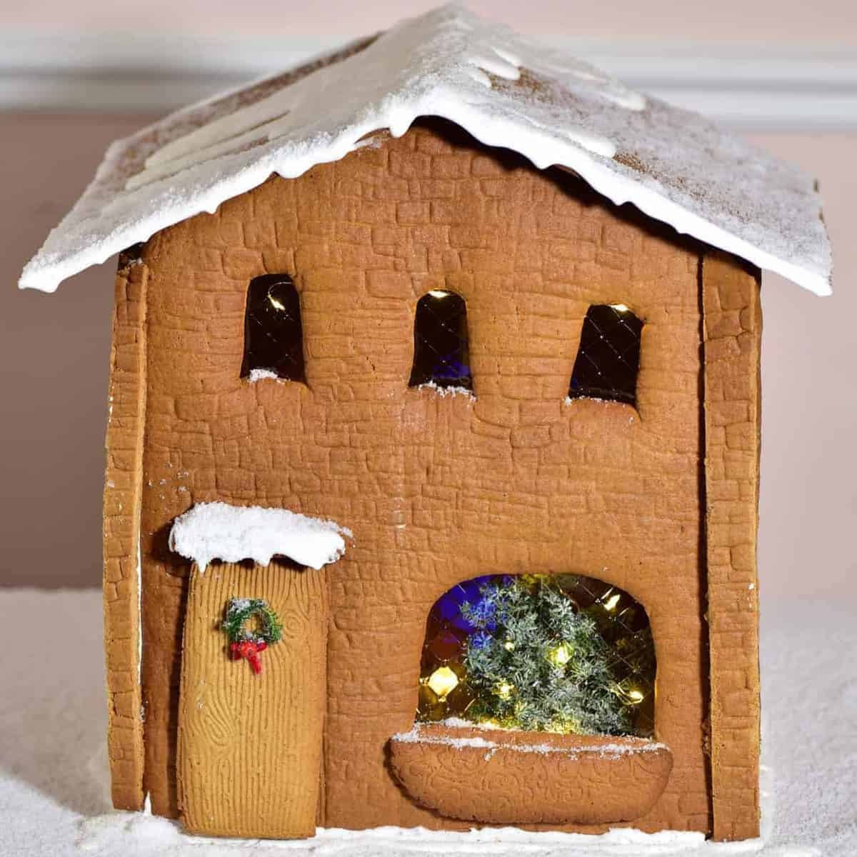 Gingerbread house decorated with a tree, lights and mini wreath