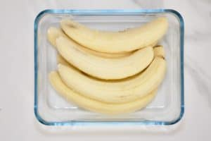 Six peeled bananas in a square glass container